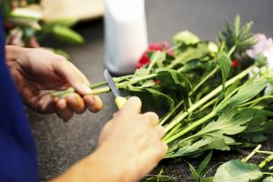 Female florist hands making bouquet in flower shop